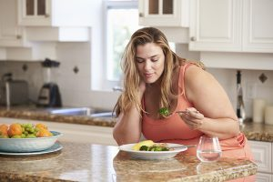 what causes obesity, woman eating