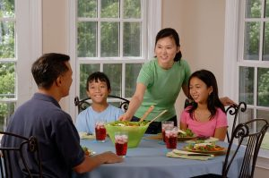 family support, a family all having healthy dinner together