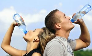 causes of fatigue, man and woman drinking bottled water