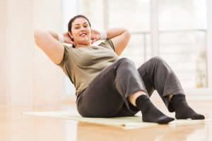 cope with plateaus, woman doing crunches.