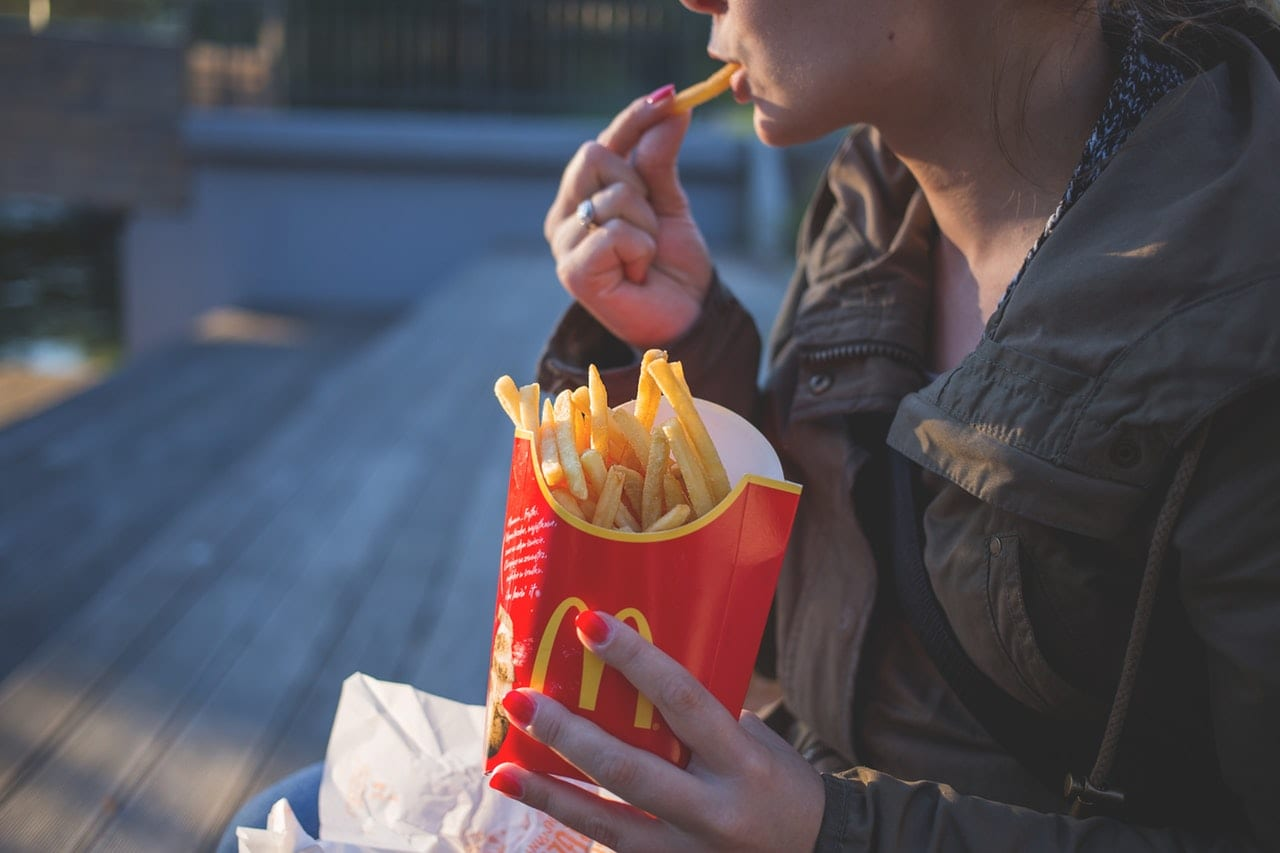Top 10 Unhealthiest Countries. Woman eating french fries