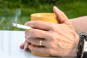 Top 10 Unhealthiest Countries. Person holding a cigarette and cup of coffee.